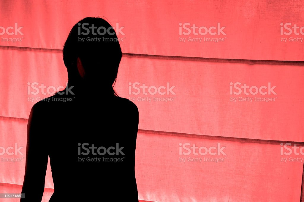Silhouetted view of woman standing at red light district stock photo