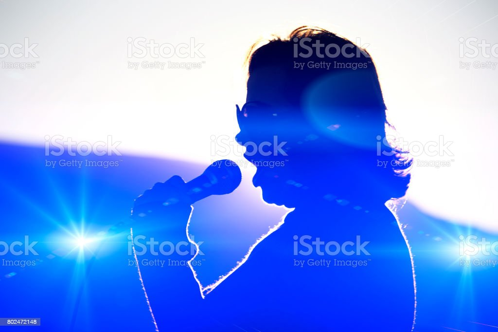 Silhouetted woman speaks into a microphone with stage lights stock photo