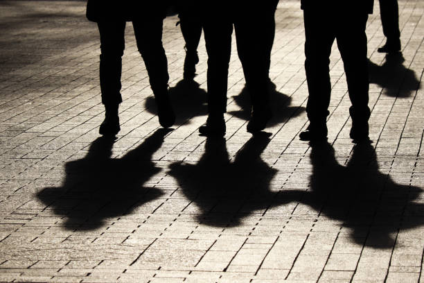 Silhouettes and shadows of people on the street Crowd walking down on sidewalk, concept of strangers, crime, society, epidemic, population crime stock pictures, royalty-free photos & images