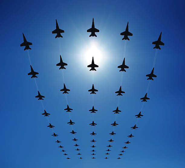 F18 silhouettes in the sky Rows of fighter jets flying in the sky. Clear sunny day. Check out some other airplane files: arrangement stock pictures, royalty-free photos & images