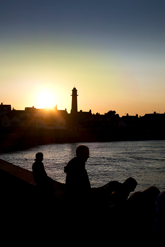 A group of people silhouetted against the glow of the setting sun on the quayside at Gorleston-on-Sea in Norfolk, Eastern England. Gorleston-on-Sea is across the River Yare from the larger coastal town of Great Yarmouth.