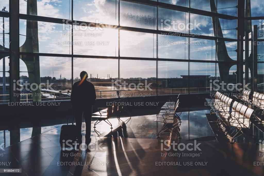 Silhouettes male tourist indoors of airport terminal stock photo