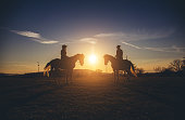 Silhouettes of a couple on horses at sunset