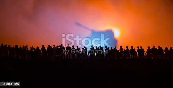 istock Silhouettes of a crowd standing at field behind the blurred foggy background. Selective focus. Revolution, people protest against government, man fighting for rights. Selective focus 923092150