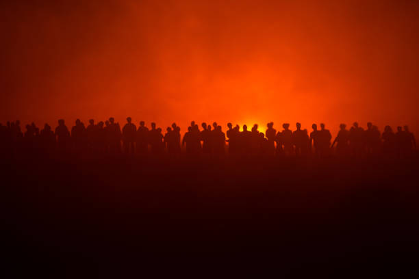 Silhouettes of a crowd standing at field behind the blurred foggy background. Revolution, people protest against government, man fighting for rights – zdjęcie