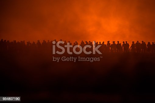 istock Silhouettes of a crowd standing at field behind the blurred foggy background. Revolution, people protest against government, man fighting for rights 934807190