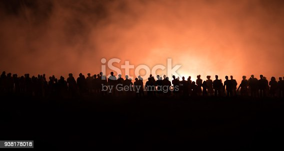 istock Silhouettes of a crowd standing at field behind the blurred foggy background. Revolution, people protest against government, man fighting for rights 938178018