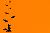 istock Silhouettes of a flock of bats and a witch flying on a broom made of black paper on an orange background. Halloween greeting template with copy space. Flat lay for your design. ready-made template 1281463288