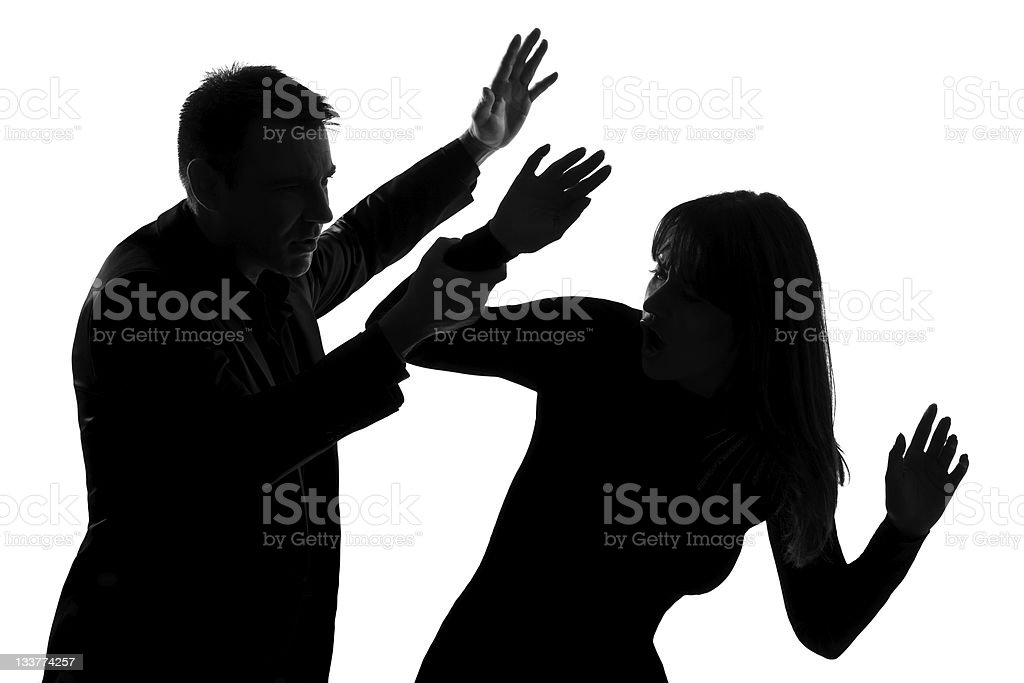 Silhouettes of a man and a woman during an altercation stock photo