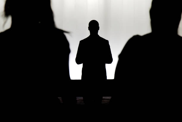 silhouettes of a mystery man standing , watching and confronting two blurry persons - preacher stock photos and pictures