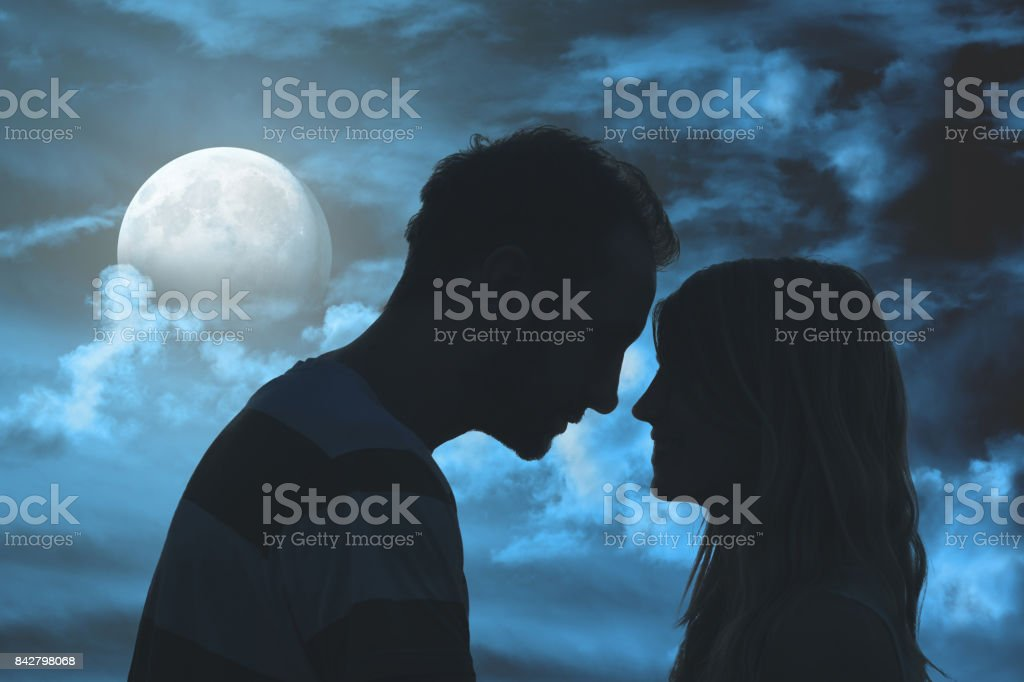 Silhouettes of a young couple under the moonlit sky. Elements of this image are my work only. stock photo