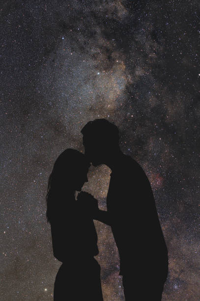 silhouettes of a young couple under the starry sky. my astronomy work. - romantic moon stock photos and pictures