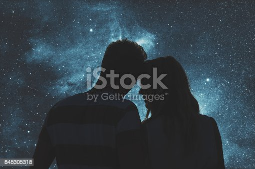istock Silhouettes of a young couple under the starry sky. My astronomy work. 845305318