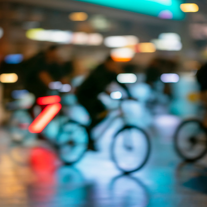 929609038 istock photo Silhouettes of abstract unrecognizable people, riding bikes, night city, illumination bokeh, motion blur. Healthy lifestyle, leisure activity concept. 1186913763