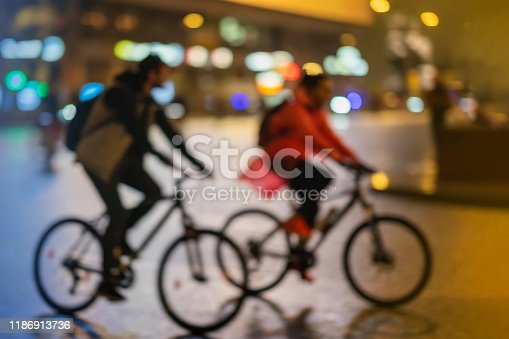 863454090istockphoto Silhouettes of abstract unrecognizable young couple, riding bikes, night city, illumination bokeh, motion blur. Healthy lifestyle, leisure activity concept. 1186913736