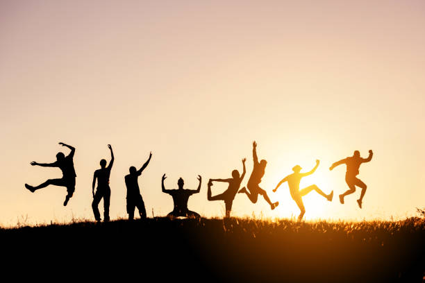 Silhouettes of big group of friends jump and fun