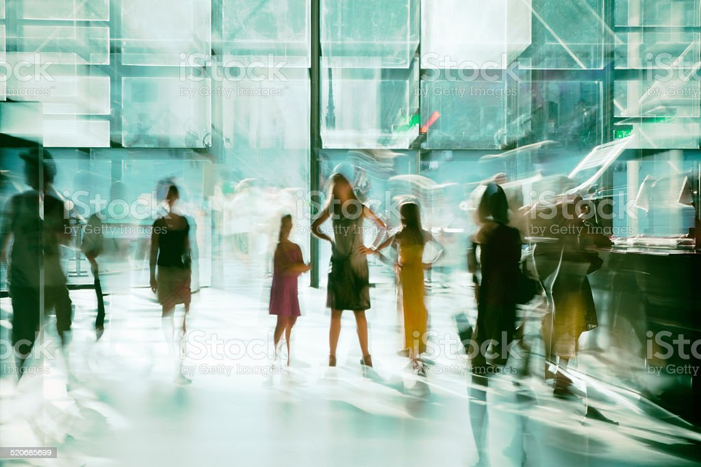 Silhouettes of Blurred People in Modern Bright Glass Interior stock photo