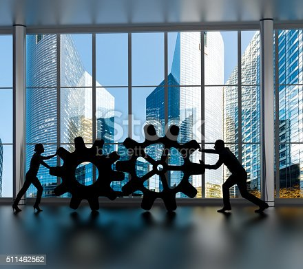 istock Silhouettes of business partners moving gears inside an office 511462562