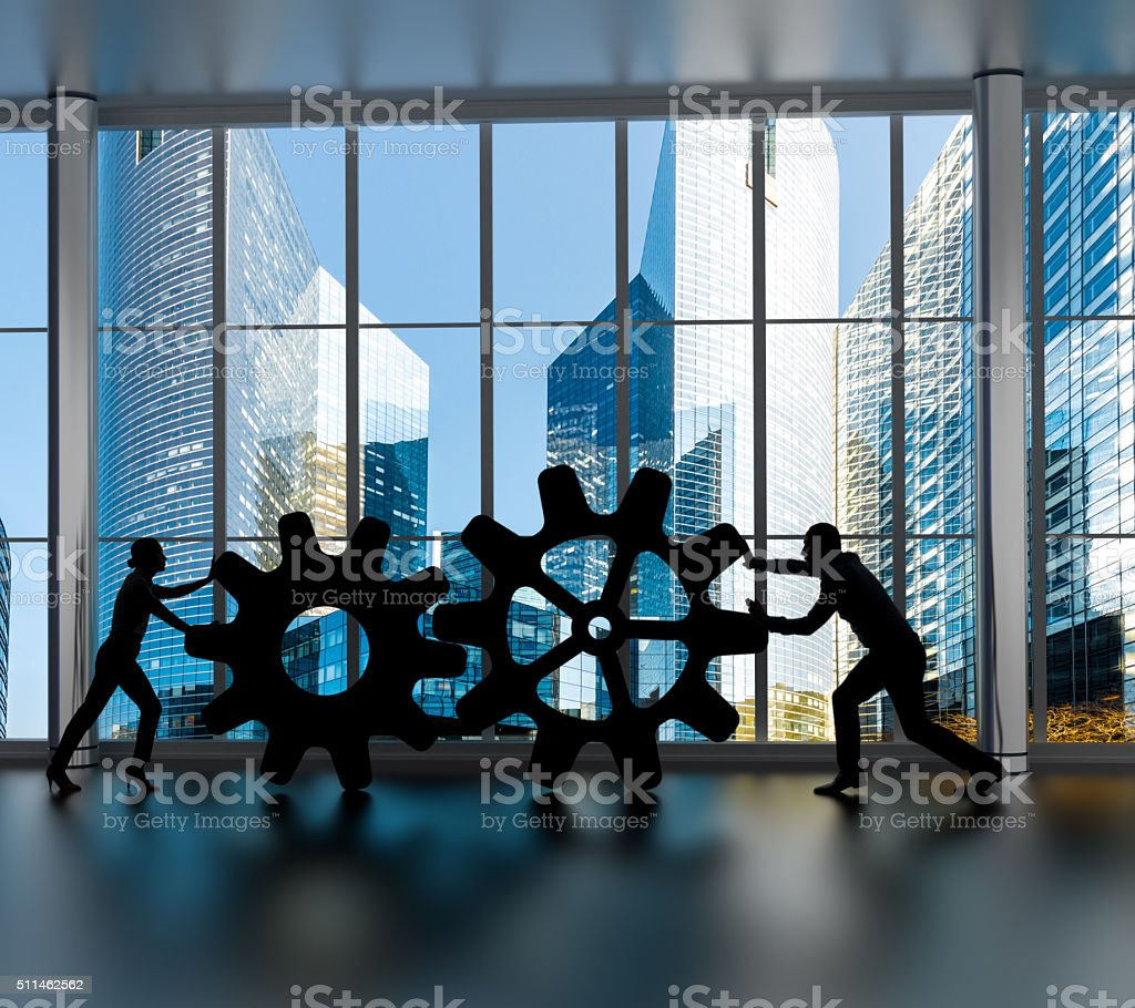 Silhouettes of business partners moving gears inside an office stock photo