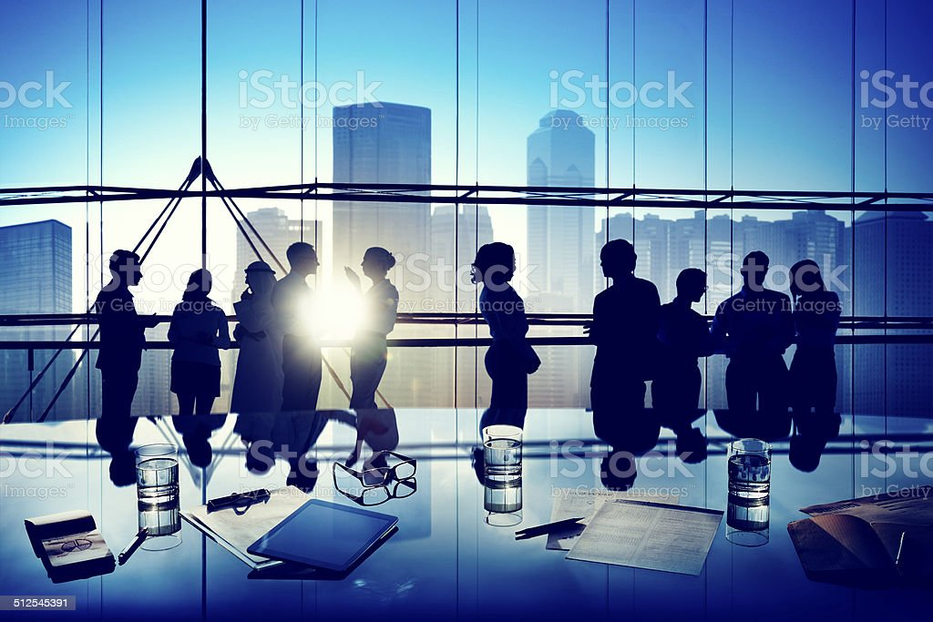 Silhouettes of Business People Gathered Inside the Office stock photo