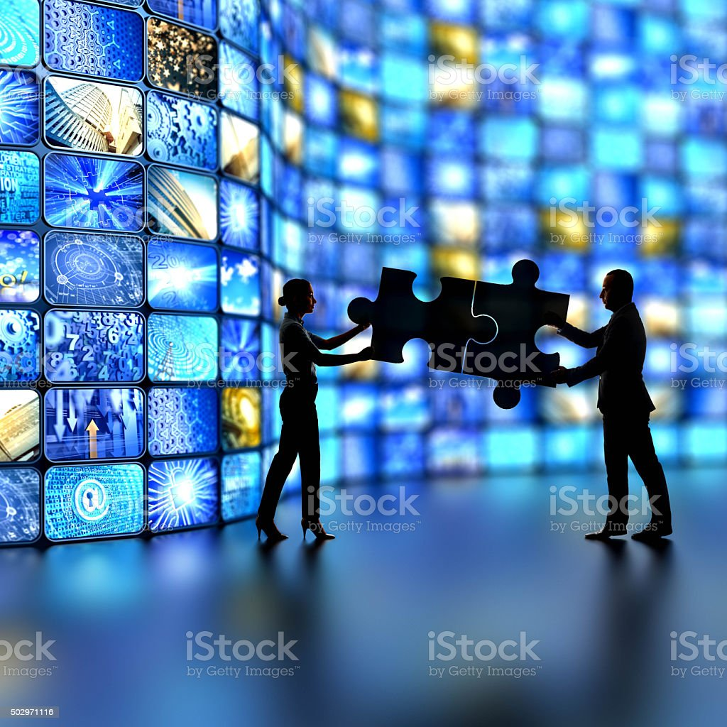 silhouettes of business people holding two giant puzzle pieces stock photo