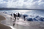 Sosua, Dominican Republic, December 24, 2016, silhouettes of children and people playing on the beach in the waves and water splashes on vacation, blue sea, waves sun light background