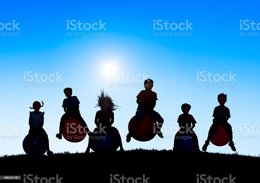 Silhouettes of Children Playing on Balls and Copy Space Above stock photo