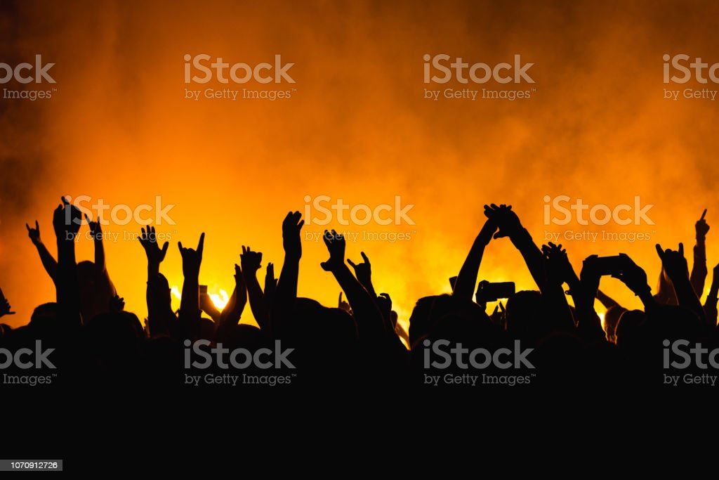 silhouettes of concert crowd in front of bright stage lights. Dancing people with hands on against stage light. Fans burn red flares at rock concert stock photo
