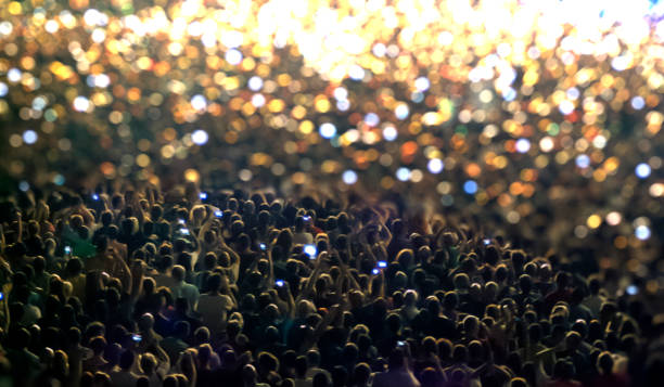 silhouettes of concert crowd in front of bright stage lights - dance group stock photos and pictures