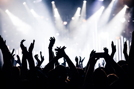istock silhouettes of concert crowd in front of bright stage lights 828105816