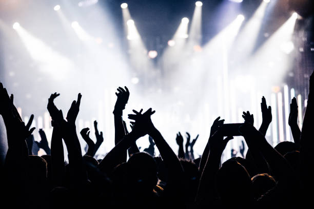 silhouettes of concert crowd in front of bright stage lights - music style stock pictures, royalty-free photos & images