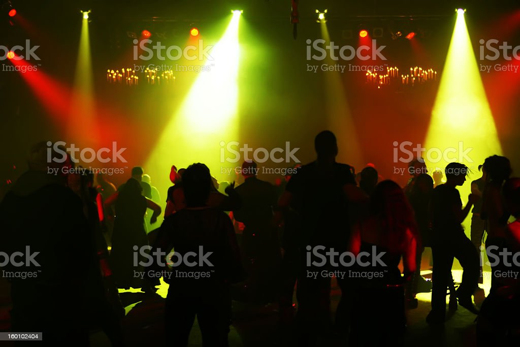 Silhouettes of dancing youths under red and green lights royalty-free stock photo