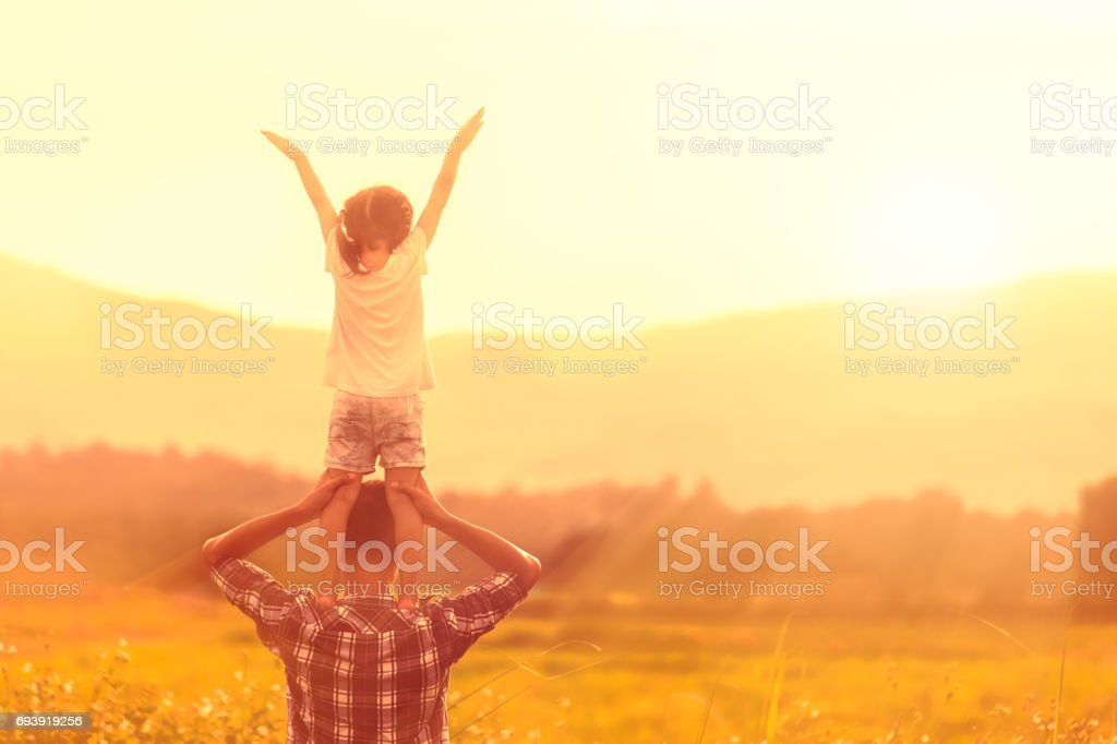 Silhouettes of father and daughter playing together in the cornfield at sunset stock photo
