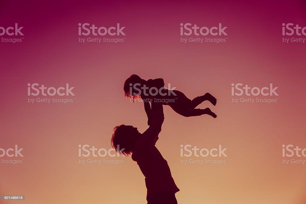 silhouettes de père et petite fille jouant au coucher du soleil photo libre de droits