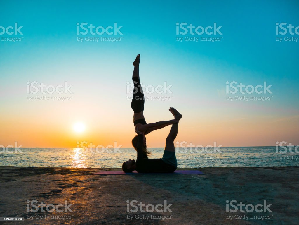 Silhouettes of fit young couple doing acro-yoga at sea beach. Man lying on concrete plates and balancing woman in his feet. Beautiful couple practicing yoga together stock photo