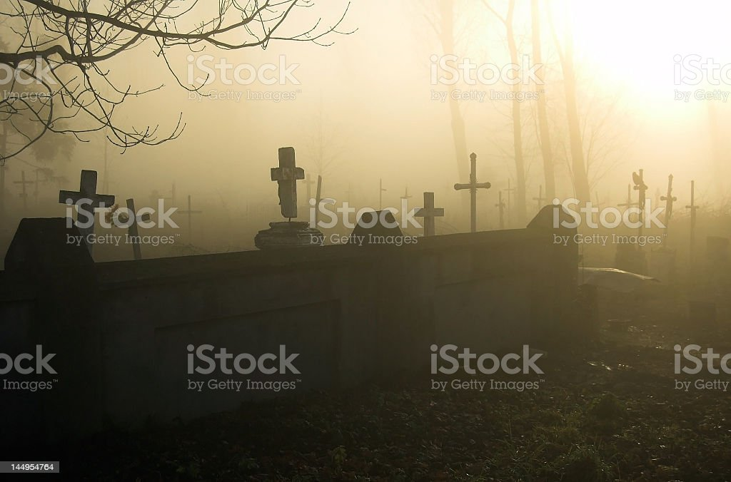 Silhouettes of graves in a misty cemetery royalty-free stock photo