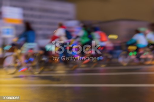 929609038istockphoto Silhouettes of Group riding colorful Cyclists in traffic on the city, abstract, motion blur, for background 929609056