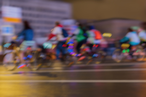 929609038 istock photo Silhouettes of Group riding colorful Cyclists in traffic on the city, abstract, motion blur, for background 929609056