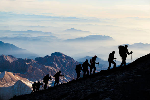 Silhouettes of hikers At Dusk stock photo