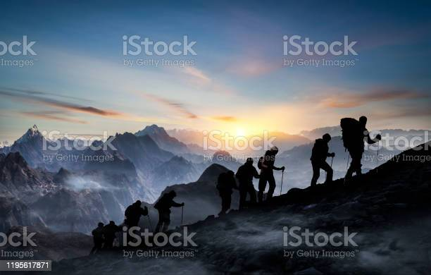 Photo of Silhouettes of hikers At Sunset