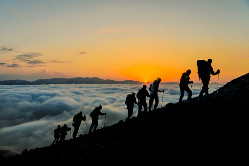Silhouettes of hikers climbing the mountain at sunset.