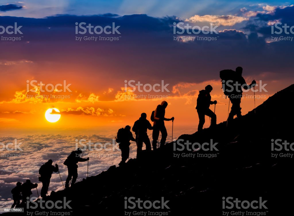 Silhouettes of hikers At Sunset stock photo