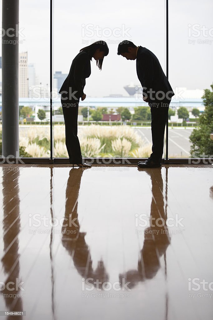 Silhouettes of Japanese businessman and businesswoman bowing to each other stock photo