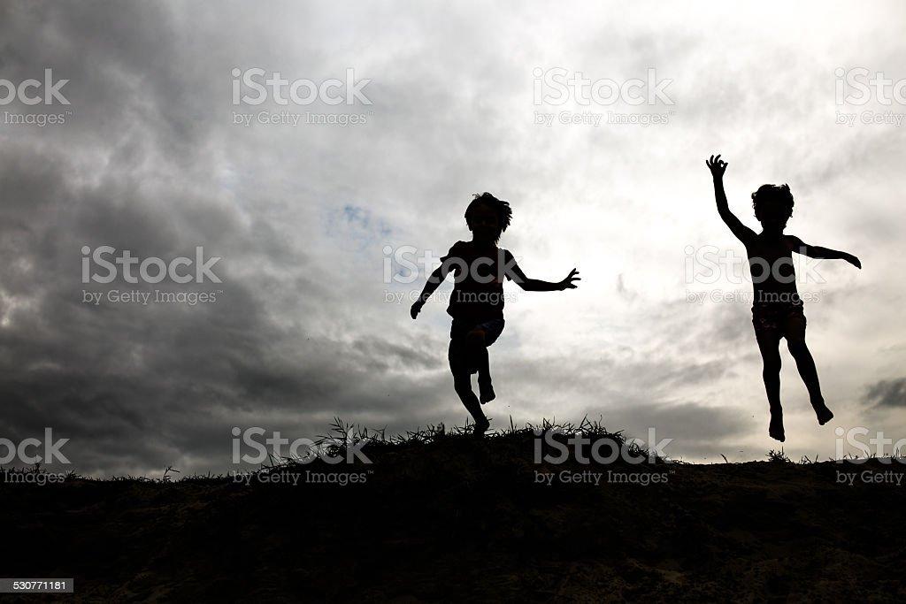 Silhouetten der Kinder springen von einer Klippe – Foto