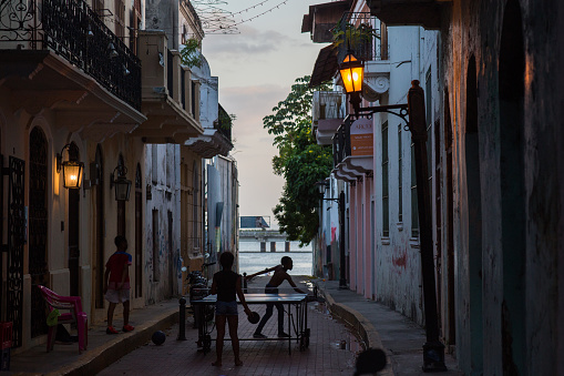 Silhouettes of kids playing table tennis in the character-rich streets of Casco Antiguo in early evening light