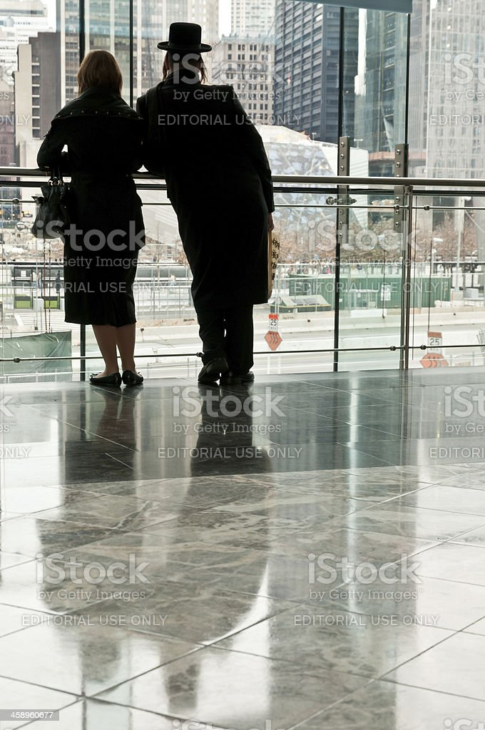 Silhouettes of man and woman looking at Freedom Tower construction stock photo