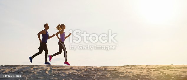 Silhouettes of male and female running at sunset on the beach