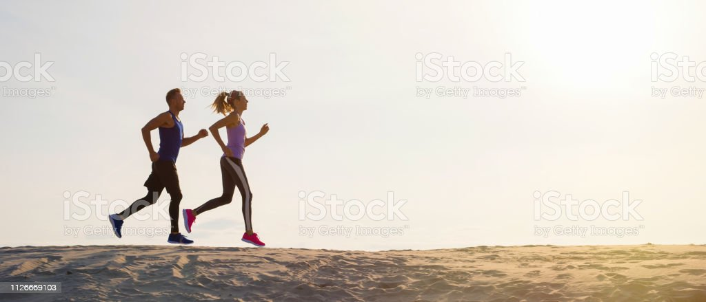 Silhouettes of man and woman running at sunset stock photo