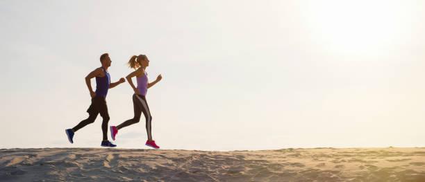 silhouettes of man and woman running at sunset - бег трусцой стоковые фото и изображения
