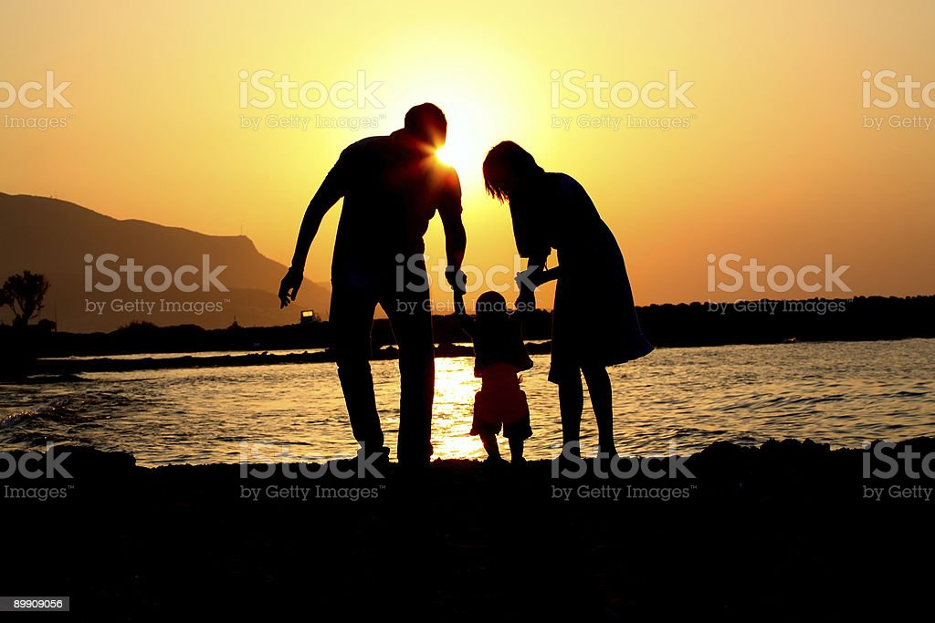 Silhouettes of man, child, and woman holding hands on beach royalty-free stock photo